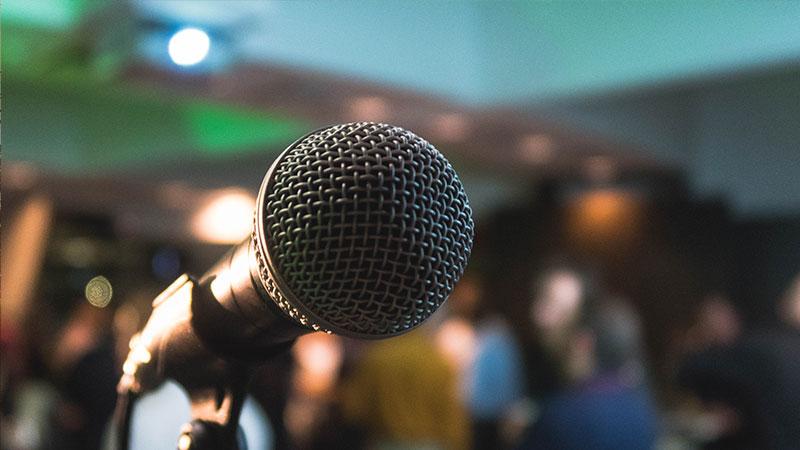 Konferens, mikrofon och människor i bakgrunden